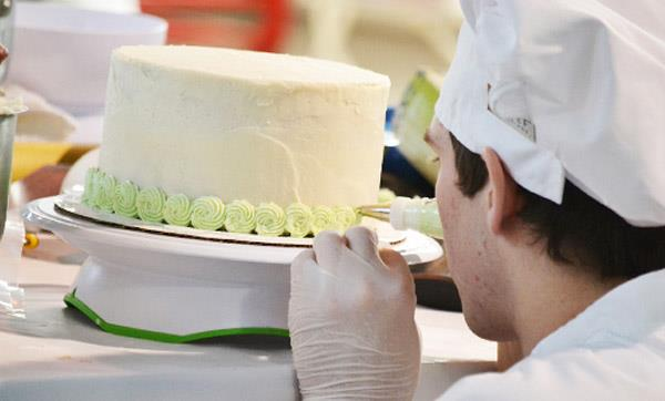 EMCC Culinary Arts student pipes decorative frosting onto a cake