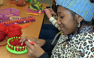 Consumer and Family Sciences student works on a tiny, red hat for Little Hats, Big Hearts.